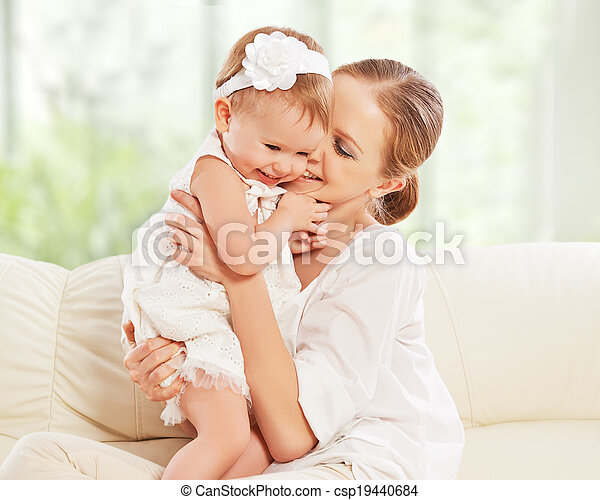 happy family. Mother and baby daughter plays, hugging, kissing at home on the sofa  - csp19440684