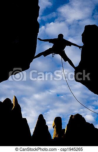 Rock climber reaching across a gap. - csp1945265