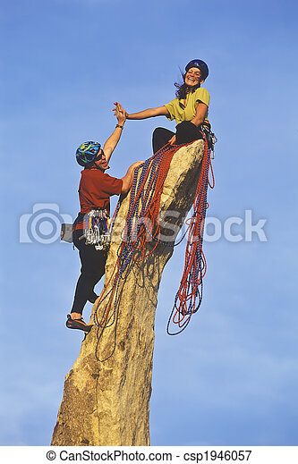 Team of rock climbers reaching the summit. - csp1946057