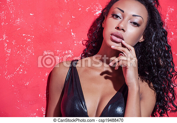 Glamour fashion model. Beautiful young Afro-American woman with make up and hairstyle posing against red background - csp19488470