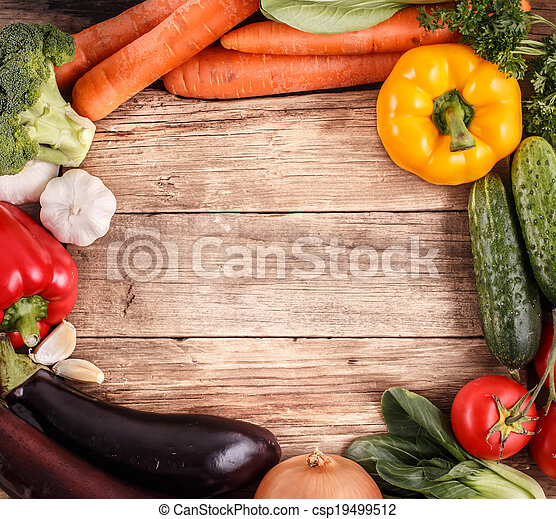 Vegetables on wood background with space for text. Organic food. - csp19499512