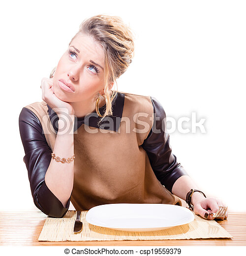 Beautiful young attractive blonde woman holding fork in her hand looking up, empty plate isolated on white background portrait