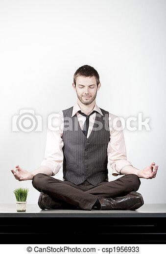 Handsome Young Businessman Meditating on Desk - csp1956933