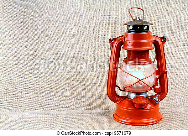 Red oil lamp on burlap and copy space