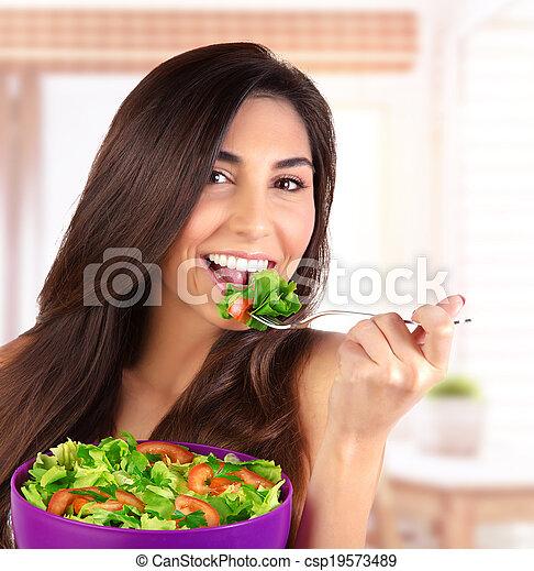 Beautiful woman eating salad - csp19573489