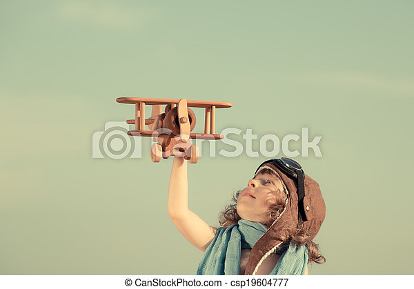 Happy child playing with toy airplane against summer sky - csp19604777