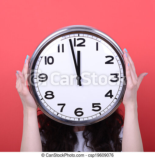 Portrait of girl holding huge office clock against red background