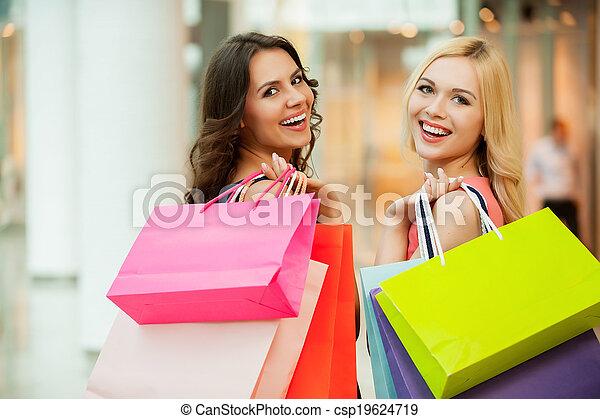 Happy friends shopping. Two beautiful young women enjoying shopping at shopping mall - csp19624719