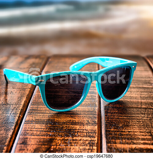 Sunglasses on wooden desk at the summer beach - csp19647680