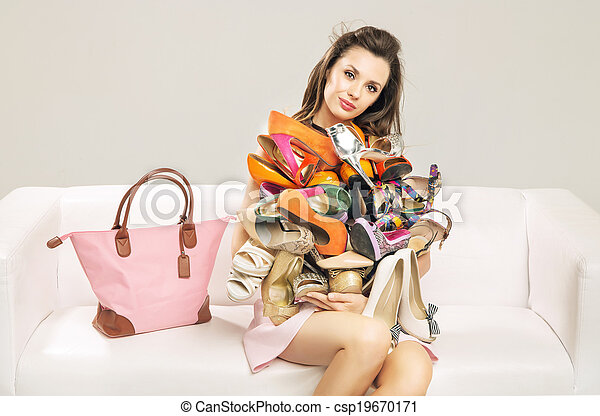 Attractive woman carrying a heap of shoes
