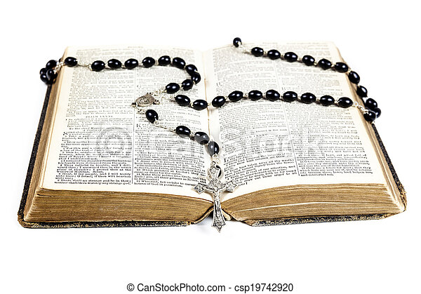Rosary beads and cross lying on an open page of the bible isolated on a white background.