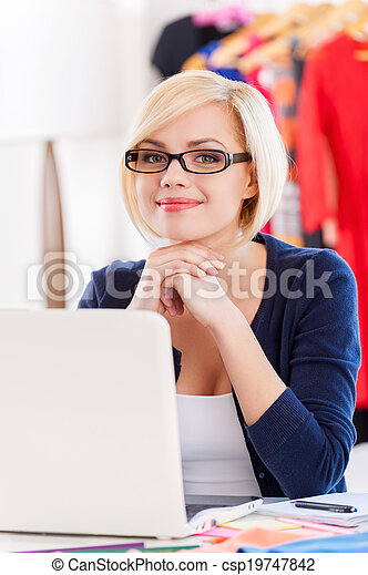 Confident and creative businesswoman. Beautiful young woman holding hands on chin and smiling while sitting at her working place - csp19747842