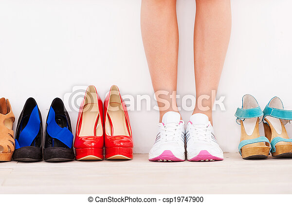 I made my choice! Cropped image of woman in sports shoes standing against the wall while high hilled shoes laying in a row near her - csp19747900