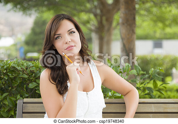 Young Adult Female Student on Bench Outdoors - csp19748340