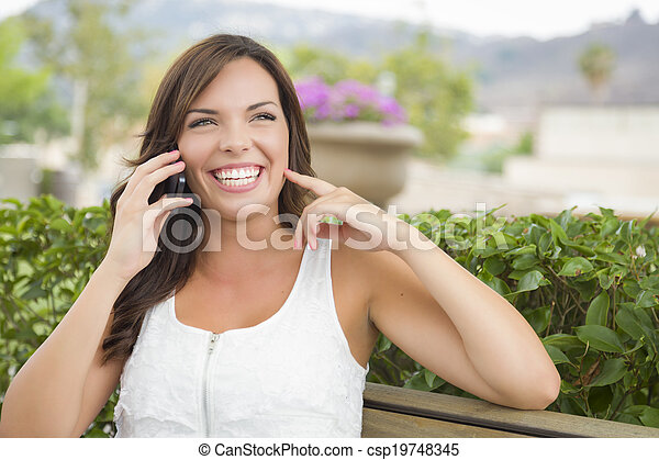 Young Adult Female Talking on Cell Phone Outdoors on Bench - csp19748345