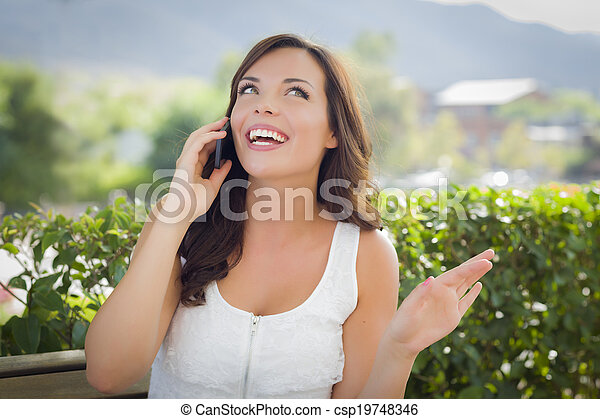 Young Adult Female Talking on Cell Phone Outdoors on Bench - csp19748346