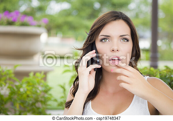 Stunned Young Adult Female Talking on Cell Phone Outdoors - csp19748347