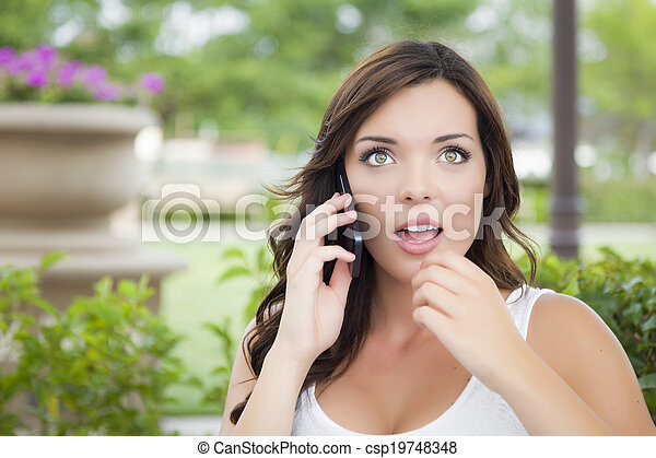 Stunned Young Adult Female Talking on Cell Phone Outdoors - csp19748348