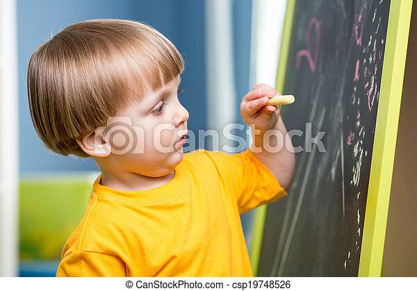 Little boy draws with chalk on blackboard