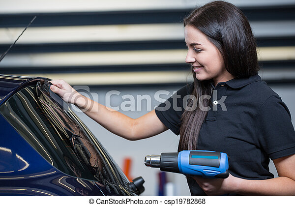 Car wrapper using heat gun and squegee for tinting window - csp19782868