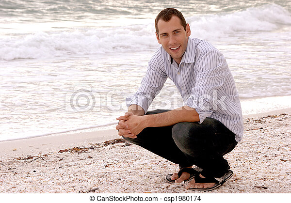 portrait of smiling handsome young adult male on the beach - csp1980174