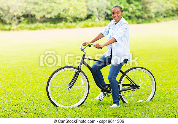 young adult african girl riding a bicycle - csp19811306