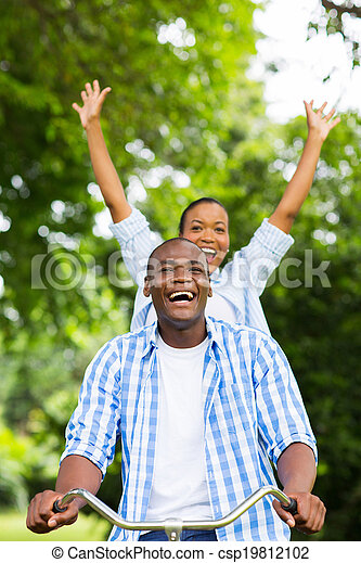 african girl riding a bicycle with boyfriend - csp19812102