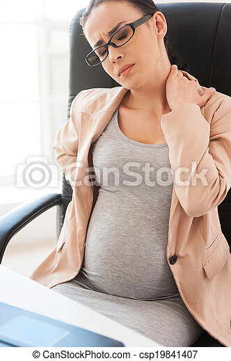Tired pregnant woman. Depressed pregnant businesswoman holding head in hand while sitting at her working place in office  - csp19841407
