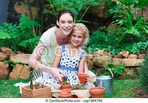 Young mother and daughter planting flowers - csp1984766