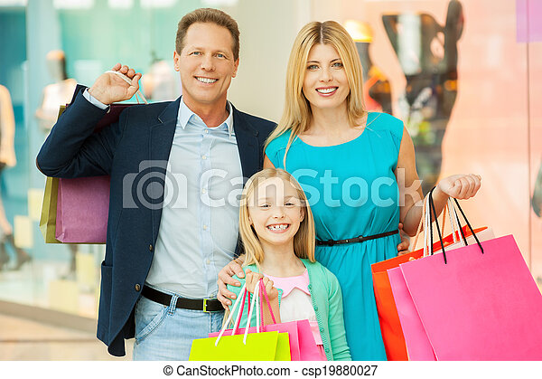 Happy family shopping. Cheerful family holding shopping bags and smiling at camera while standing in shopping mall