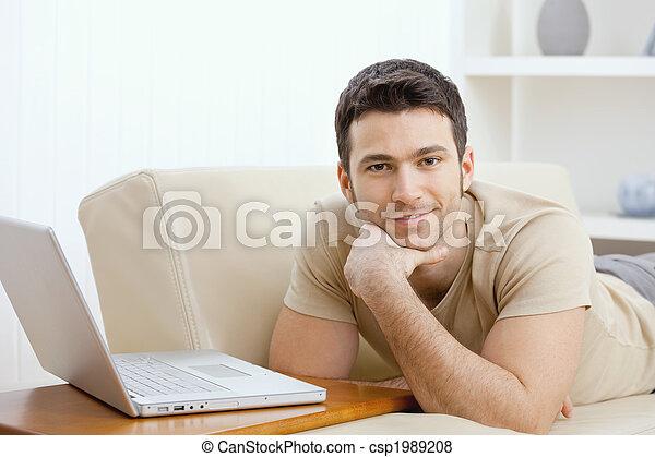 Man using laptop at home - csp1989208