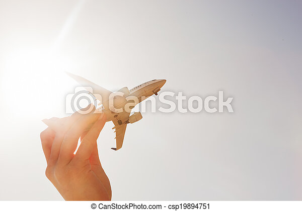 Airplane model in hand on sunny sky. Concepts of travel, transportation - csp19894751