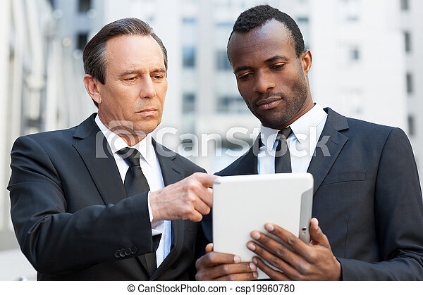 Consulting with expert. Two confident business men looking at the digital tablet while one of them pointing it with finger