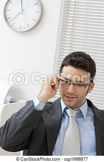 Businessman taking off glasses - csp1998877