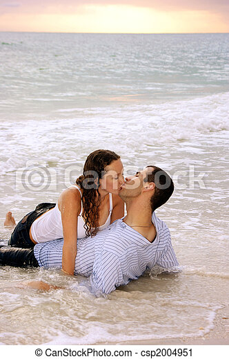 lovers being swept away with kiss and the tide - csp2004951