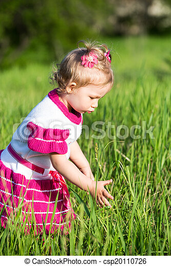 Portrait of little child girl on grass on meadow. Summer green nature background