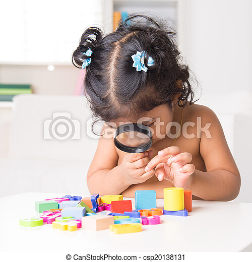 Indian girl zoom into toys through a magnifying glass - csp20138131