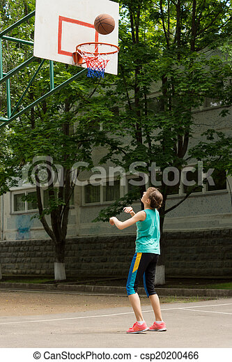 Young girl shooting a goal in basketball