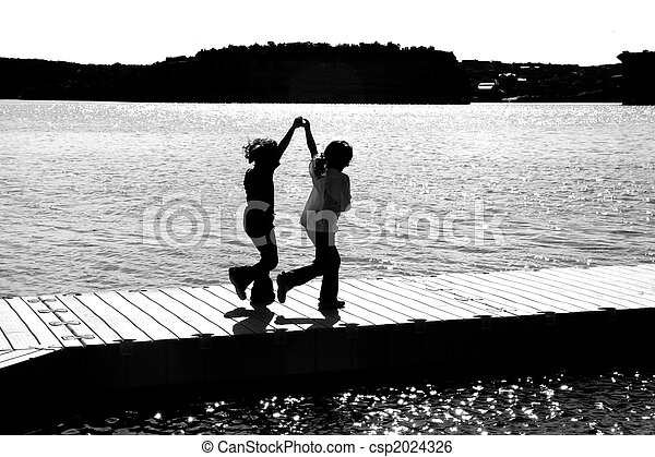 Silhouette of Two Young Girls Playing on a Dock - csp2024326
