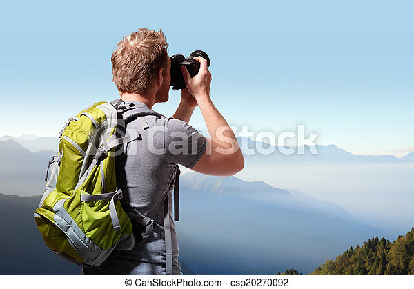 Young man taking photo on top of mountain - csp20270092