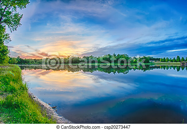 sun setting over a reflective lake - csp20273447