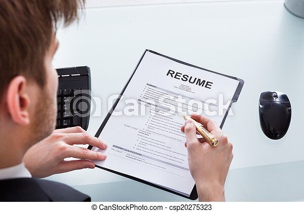 Businessman Analyzing Resume At Office Desk - csp20275323