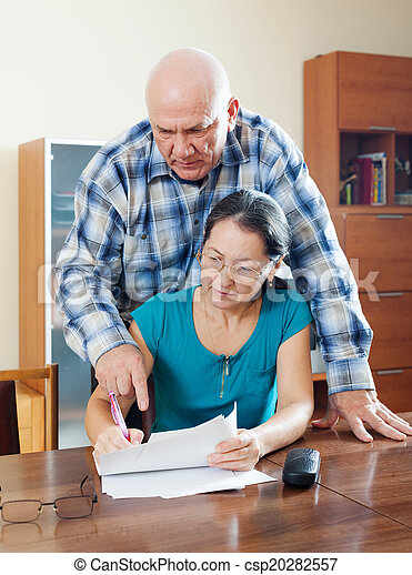 Stock Images of serious senior man with mature wife fills in ...