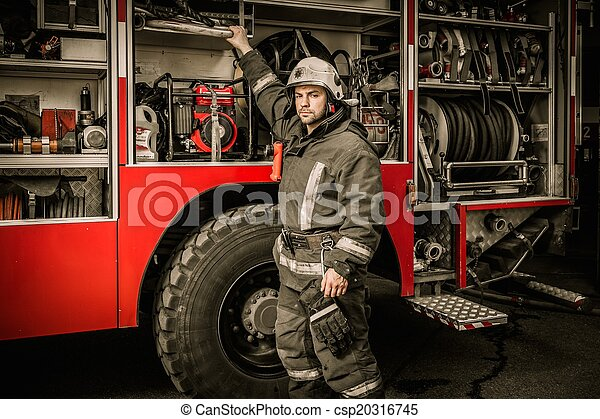 Fireman taking equipment from firefighting truck  - csp20316745