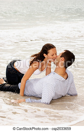 beautiful couple kissing in the tide - csp2033659