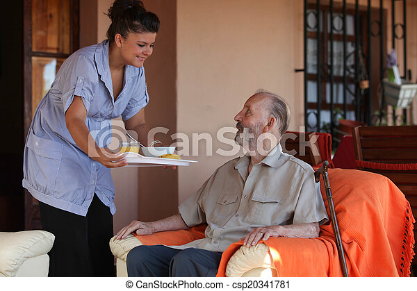 nurse or helper in residential home giving food to senior man - csp20341781