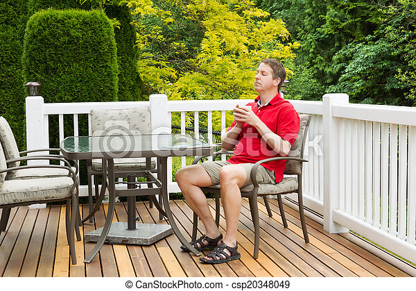 Mature man resting in chair on outdoor patio with cup of coffee
