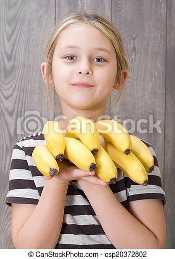 girl holding a bunch of bananas