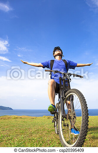 close-up man sitting on a  mountain bike and open arms to relax - csp20395409