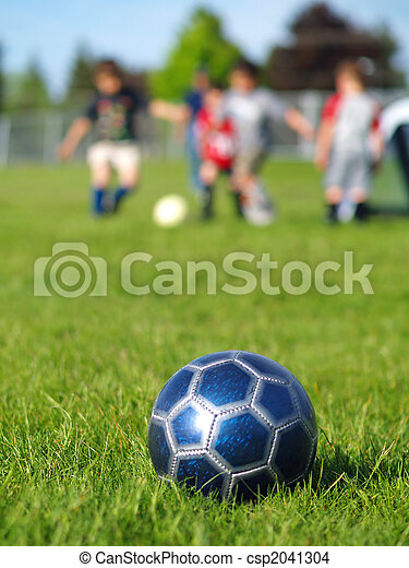 A blue soccer ball on field of green grass on a sunny day with kids in the background.